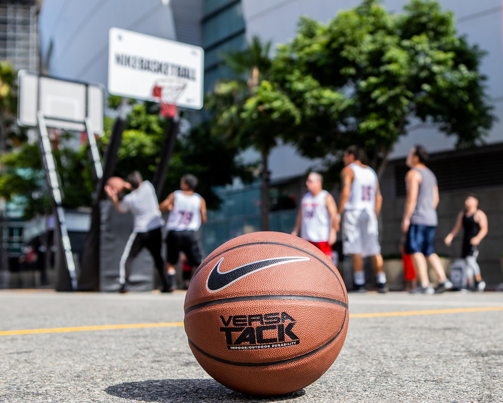 A Nike-branded basketball lies on the asphalt, while a Nike 3-on-3 game takes place out of focus in the background.